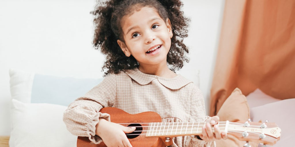 Photograph of a young child playing a ukulele